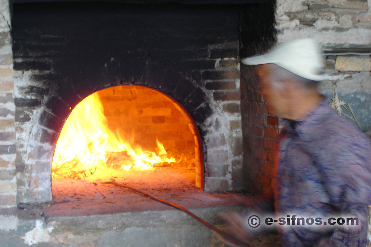 Preparing the wood oven, for the traditional easter food mastelo, in Sifnos
